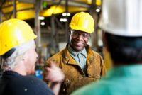 Multi-ethnic workers wearing hard hats, talking