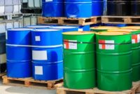 Big green and blue barrels standing on wooden pallets on a chemical plant