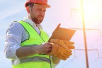 Electrician working safely near power lines on hot summer day