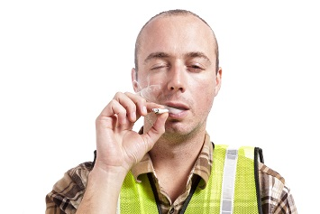 A young man in construction safety vest smokes a marijuana cigarette.