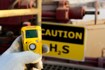 Oilfield technician checking H2S gas with his pocket type H2S Gas detector at well head in oilfield
