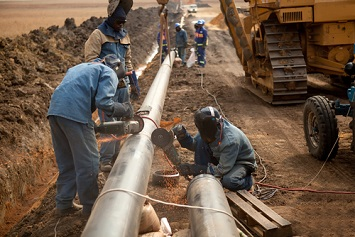Workers wearing protective clothing fixing welding and grinding industrial construction oil and gas pipeline.
