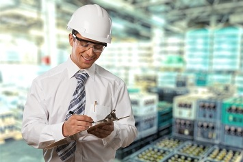 Safety professional or OSHA inspector looking at a report on a clipboard