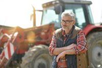 Older farmer or farm worker with a tractor