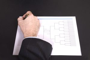 March Madness Businessman Hand Filling In Bracket From Above