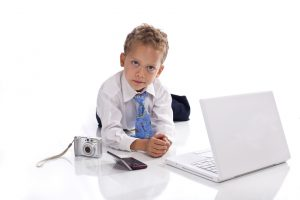 Young boy dressed as businessman with electronic gadgets