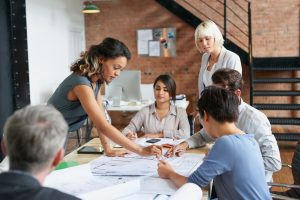 Multi ethnic group architects working on plans at business boardroom
