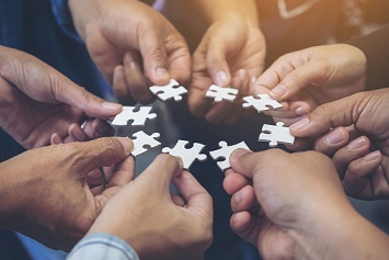 Closeup image of many people hands holding a jigsaw puzzle in circle together
