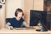 Screaming preteen boy in headset with computer playing game at home.