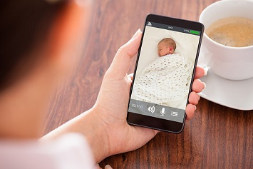 Close-up Of Woman Looking At Baby Monitor Feed On Mobile Phone