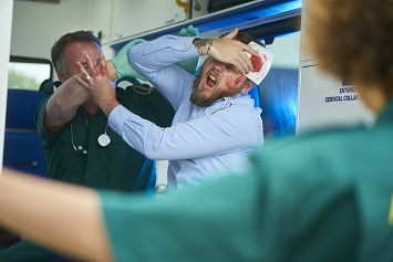 two ambulance paramedics stabilise an assault victim. They are wearing green ambulance uniform typical of uk paramedics. One is sitting in the back of the car stabilising the victim's head whilst the other paramedic is closing the door of the ambulance . The victim has been out drinking and has either fallen or been in a fight , and is acting aggressively towards the paramedic.