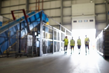 Four figures walking in an industrial interior, soft focus