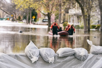 Flood Protection Sandbags with flooded homes and businesses in the background