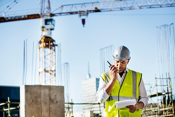 Architect using walkie-talkie while reading document at construction site