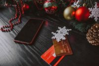 credit cards and a smartphone surrounded by Christmas decorations