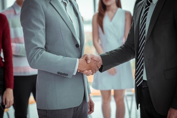 Business people shaking hands on an M&A deal.