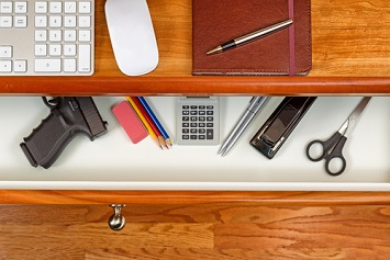 Handgun concealed in office desk