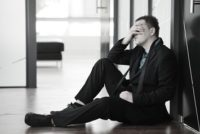 Depressed businessman distraught on office floor