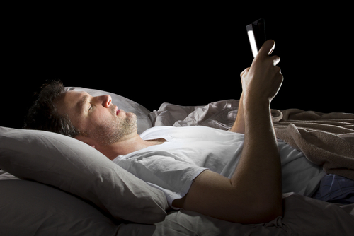 Man checking work email in bed