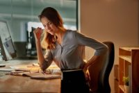 Businesswoman holding her back in pain while working at her desk
