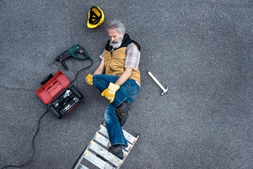 Worker lying after falling from a ladder, accident injury