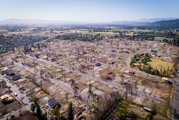Drone photo shows fire damage in the Coffey Park neighborhood eight months after wildfires destroyed the neighborhood. Only a handful of homes have been rebuilt.