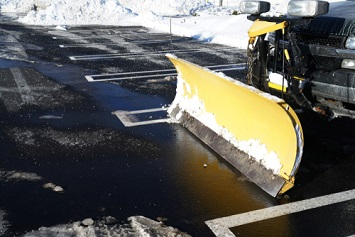 Snow plow in a facility's cleared parking lot