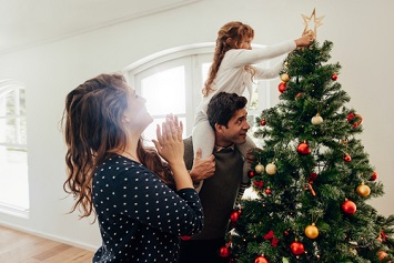 Father with daughter on his back while decorating a tree