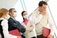 Office workers in surgical masks with coughing coworker.