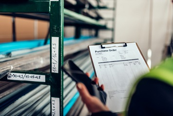 Female warehouse clerk using phone and looking at purchase order