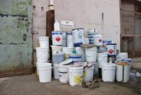 Hazardous Waste containers stacked outside facility