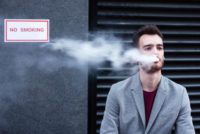 Businessman vaping in front of faciliy