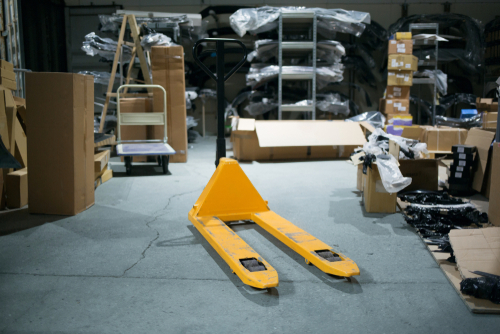 Manual pallet jack in the middle of a cluttered warehouse