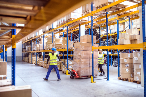 Warehouse workers moving a pallet truck