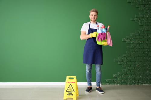 Male janitor with green cleaning supplies near wet floor sign